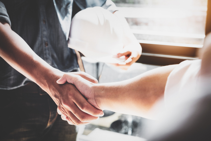 Builder holding a hard hat shaking someone's hand