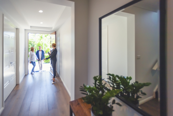 woman greeting a couple entering a house with a mirror in the hallway and a plant