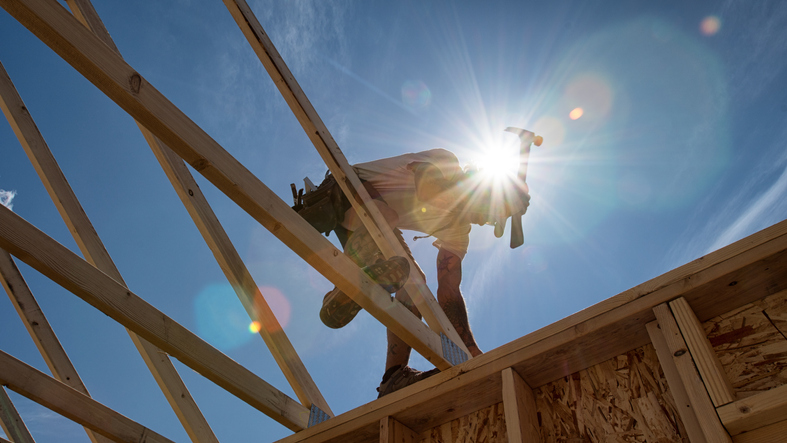 builder holding a hammer on some wooden scaffolding in the sun