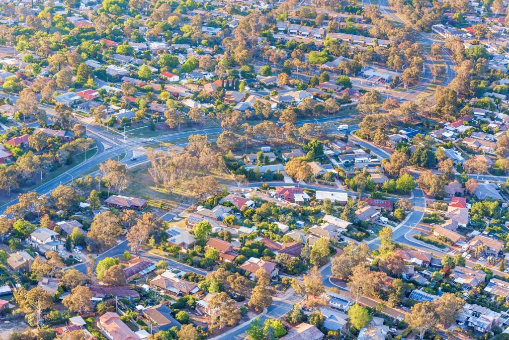 above shot of homes in Canberra with streets and trees visible
