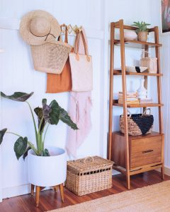 interior design of a rental revamp with plant, towels and a wooden clothes rack