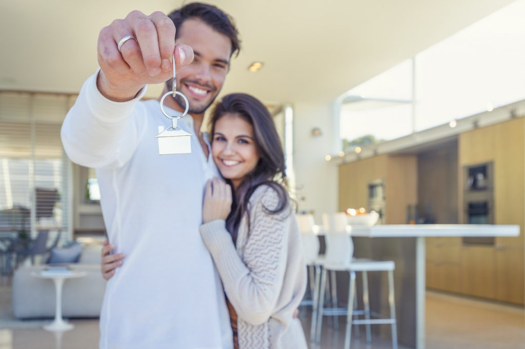 home buyer holding a house key in their new home. They are standing in their new modern house. Both are happy and smiling. The house key has a house icon keyring