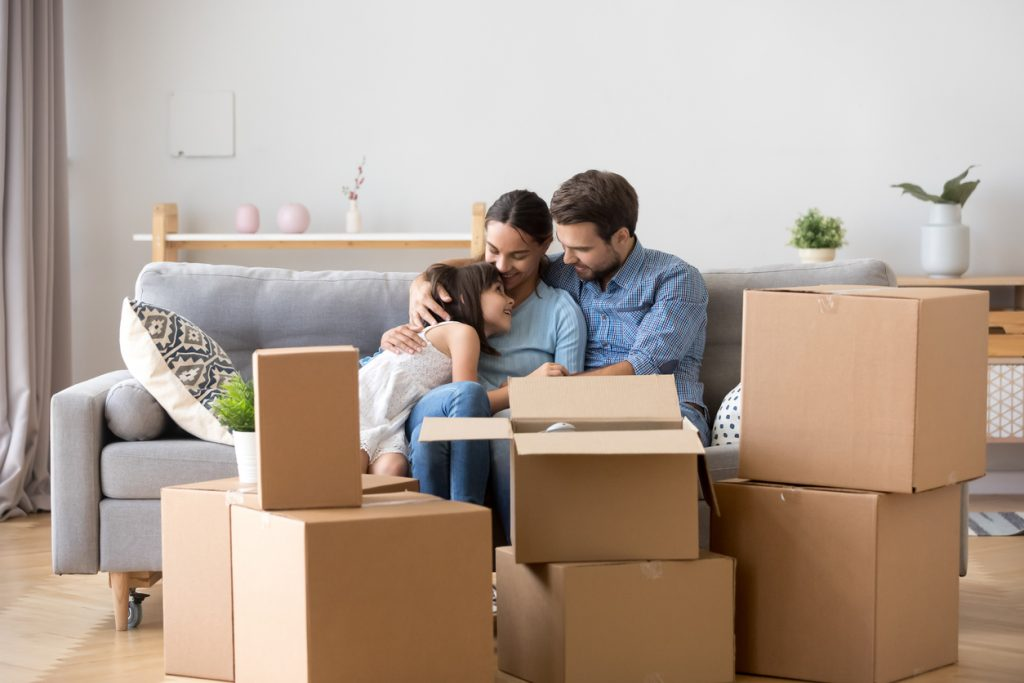 Diverse family parents and little daughter sitting together on sofa in living room at new home. People surrounded by carton boxes resting indoors. Buy new house and improve living conditions concept