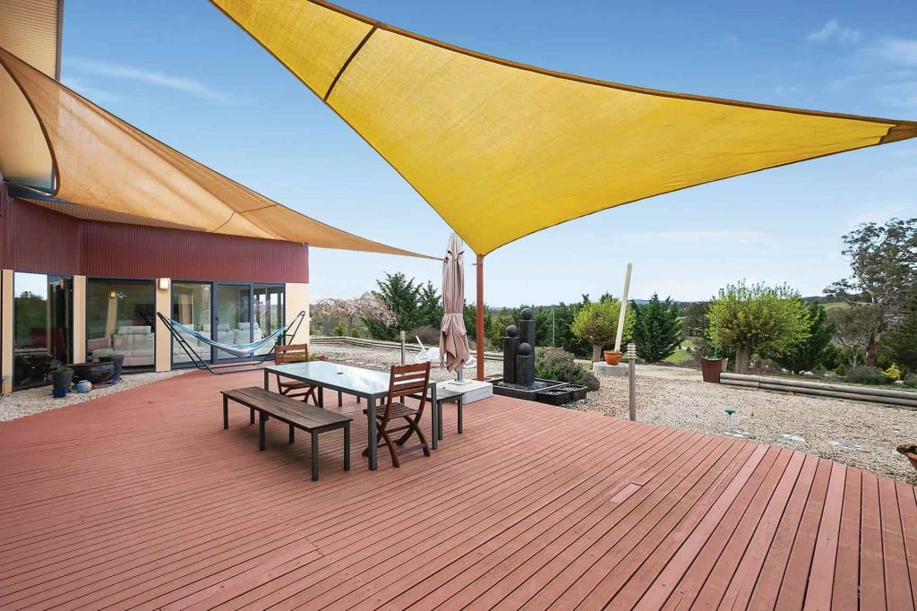 deck of home with large yellow shade cloth